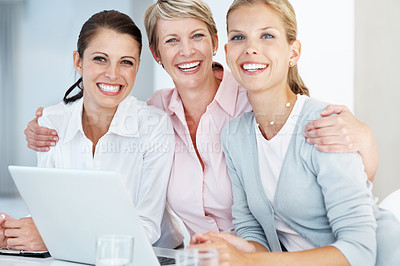 Buy stock photo Group of three confident businesswoman smiling together while working on laptop at office