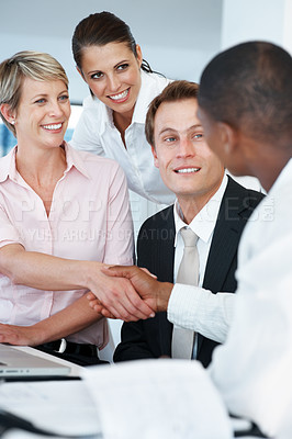 Buy stock photo Portrait of a happy young businesswoman congratulating her business colleague at office