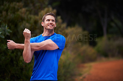 Buy stock photo Shot of a man out stretching before a run in the woods