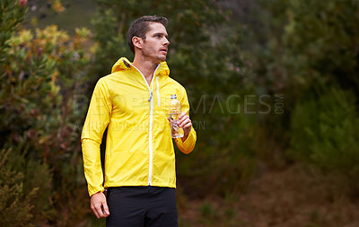 Buy stock photo Shot of a man drinking after while out for a run in the woods