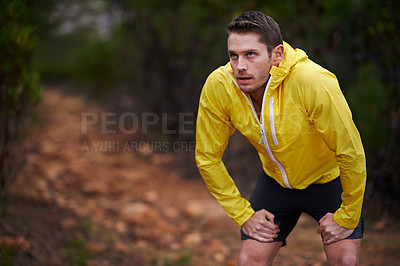 Buy stock photo Shot of a man taking a breather while out for a run in the woods