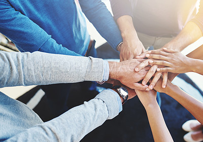 Buy stock photo Cropped shot of a group of businesspeople standing in a huddle with their hands stacked