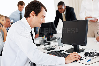 Buy stock photo Portrait of a happy young businessman working on the computer at office