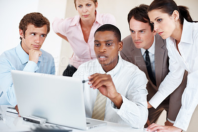 Buy stock photo African American business man with team in background working on laptop during meeting
