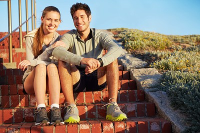 Buy stock photo A young couple sitting on the stairs taking a break from their morning jog