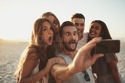 Buy stock photo Shot of a group of friends taking a selfie on the beach