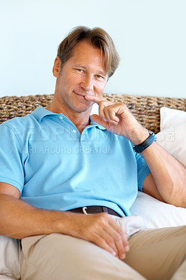 Buy stock photo Portrait of smart man sitting on a sofa at home and smiling