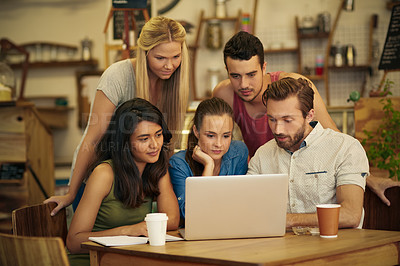 Buy stock photo A group of friends hanging out in a coffee shop with a laptop amongst them