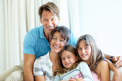 Buy stock photo Attractive family of four sitting together on a sofa and smiling