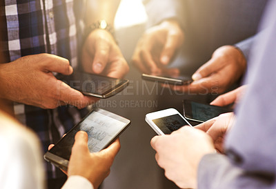 Buy stock photo Shot of coworkers using their digital devices in synchronicity