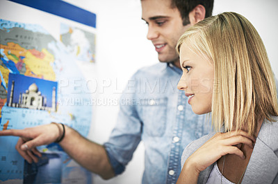 Buy stock photo Shot of a young couple planning an overseas trip