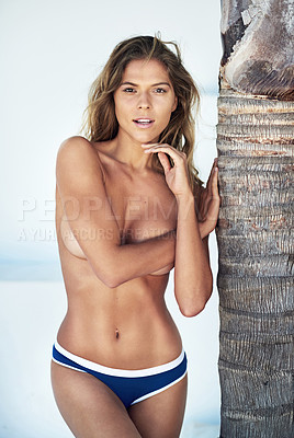 Buy stock photo Cropped portrait of a topless young woman leaning against a tree outdoors