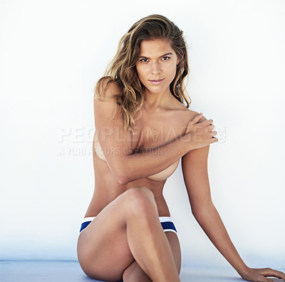 Buy stock photo Cropped portrait of a topless young woman sitting against a white wall