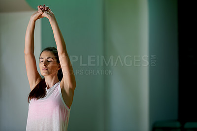 Buy stock photo Shot of a young woman doing stretches before her workout