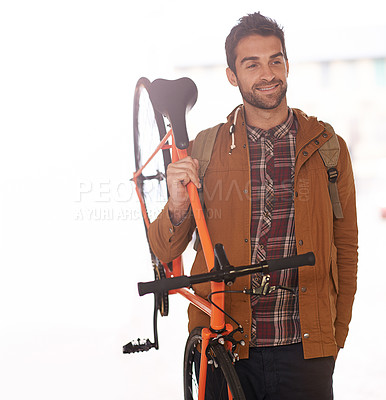 Buy stock photo Cropped shot of a young man carrying his bicycle