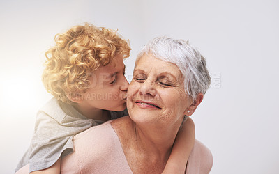 Buy stock photo Shot of a little boy giving his grandmother a kiss on the cheek