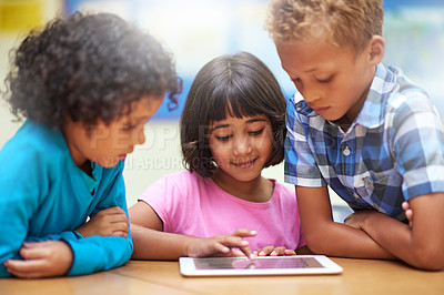 Buy stock photo Shot of elementary school children using a digital tablet while sitting in class