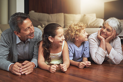 Buy stock photo Shot of grandparents spending time with their grandchildren at home