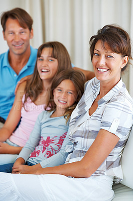 Buy stock photo Portrait of beautiful woman sitting on a sofa with her family and smiling
