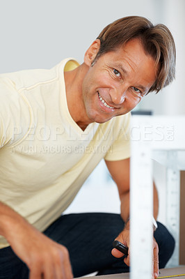 Buy stock photo Portrait of smiling man using measuring tape in the process of constructing a shelf