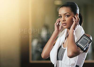 Buy stock photo Shot of a young woman listening to music while working out at the gym