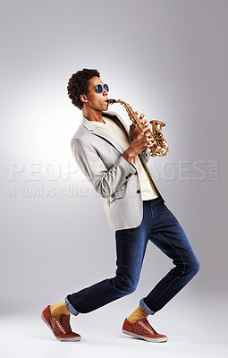 Buy stock photo Studio shot of a fashionable young man playing the saxophone