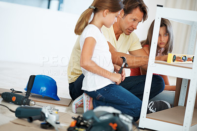 Buy stock photo Man using a digital angle meter and showing the reading to his daughters