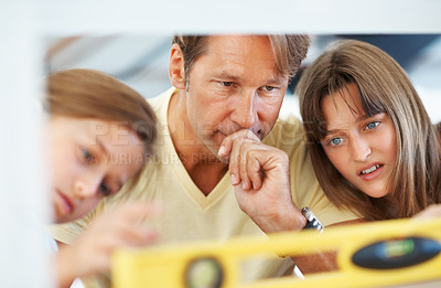 Buy stock photo Closeup of father and his daughters looking at the digital angle meter reading