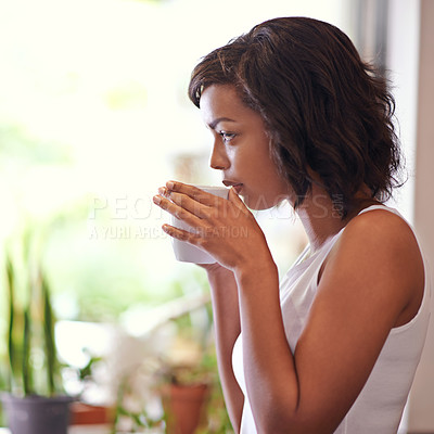Buy stock photo Shot of a young woman drinking a beverage at home