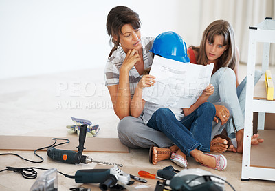 Buy stock photo Full length of family building a shelf with young girl reading instructions