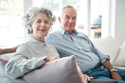 Buy stock photo Cropped portrait of a senior couple sitting on the sofa at home