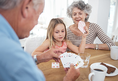 Buy stock photo Shot of a little girl playing a card game with her grandparents
