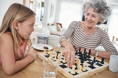 Buy stock photo Shot of a little girl playing chess with her grandmother
