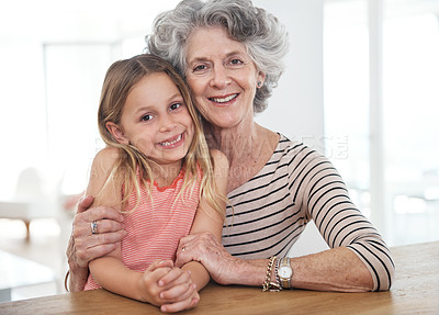 Buy stock photo Cropped portrait of a young girl and her grandmother sitting together indoors