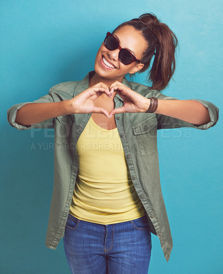 Buy stock photo Shot of a young woman making a heart shape with her hands