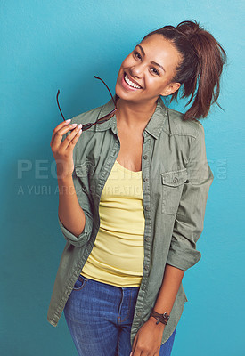 Buy stock photo Portrait of a young woman posing against a blue background