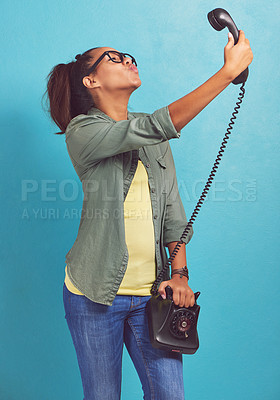 Buy stock photo Shot of a young woman talking a selfie on an old fashioned telephone