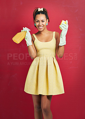 Buy stock photo Studio shot of a young woman holding a spray bottle and sponge against a red background