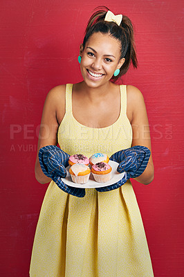 Buy stock photo Studio shot of a young woman holding a plate of cupcakes against a red background