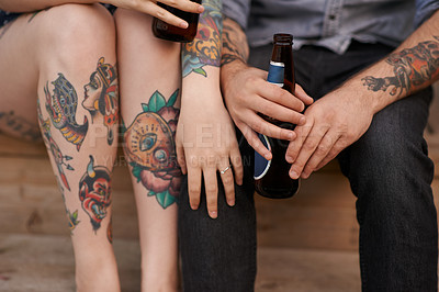 Buy stock photo Cropped shot of a couple with tattoos on their bodies and drinks in the hands