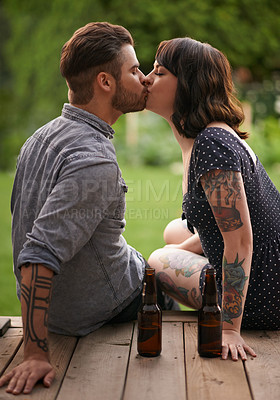 Buy stock photo Shot of a young couple sharing a kiss on the porch