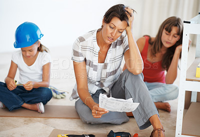 Buy stock photo Woman building a shelf with her daughters and reading instructions