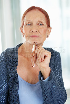 Buy stock photo Portrait of a thoughtful senior woman while holding glasses in hand