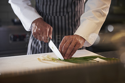 Buy stock photo Cropped shot of a chef chopping up some vegetables in the kitchen