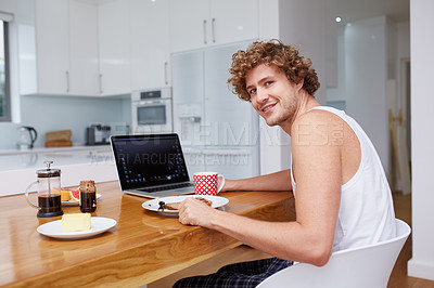 Buy stock photo A young man having breakfast while sitting with his laptop at home