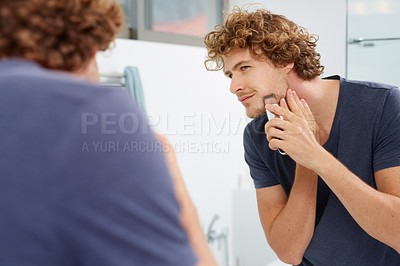 Buy stock photo A young man shaving in front of the bathroom mirror