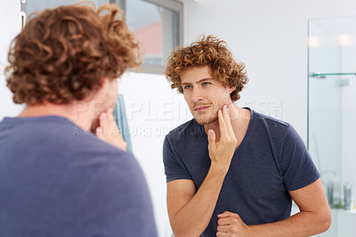 Buy stock photo A young man looking at his reflection in the bathroom mirror