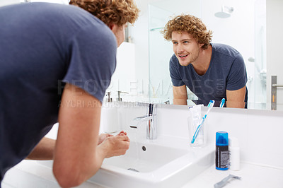 Buy stock photo A young man washing his face in the bathroom
