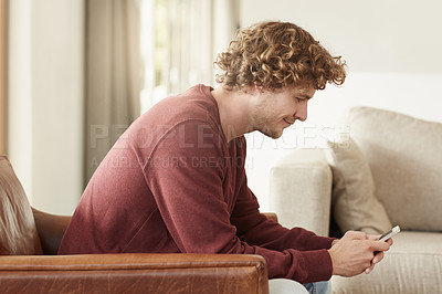 Buy stock photo Shot of a young man sending a text while sitting in his living room