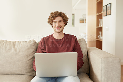 Buy stock photo Shot of a young man browsing the internet on his living room sofa